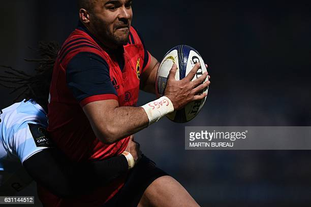 Munster Rugby's fullback Simon Zebo is tackled by Racing 92's winger Teddy Thomas during the European Champions Cup rugby union match between Racing...