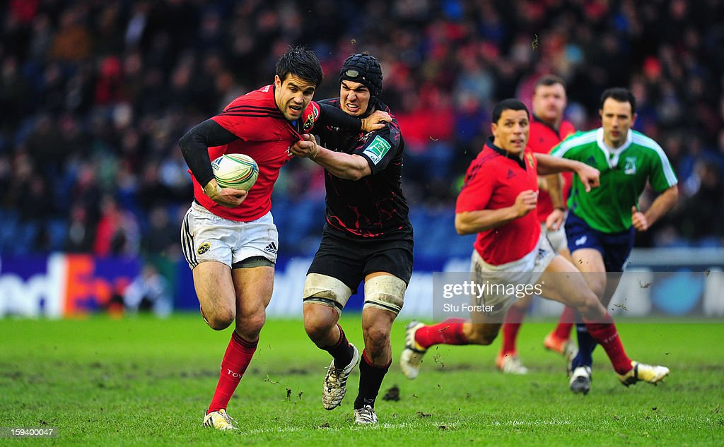 Munster scrum half Conor Murray (l) breaks the tackle of Stuart McInally during the Heineken Cup Round 5 match between Edinburgh and Munster at Murrayfield Stadium on January 13, 2013 in Edinburgh, Scotland.