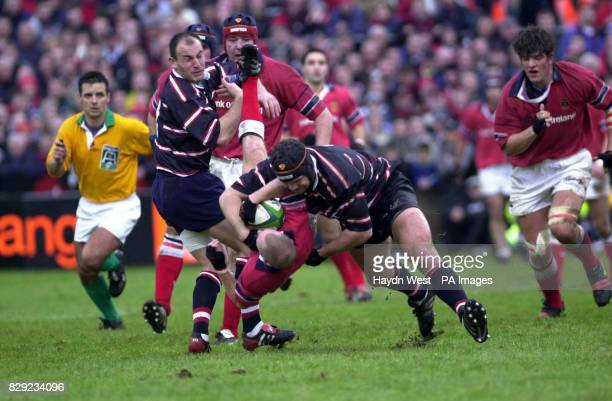 Munster scrum half Peter Stringer is upended whilst in possesion by Gloucester's Ludovic Mercier and Jake Boer in the first half of their Heineken...
