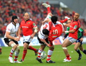 Munster's Felix Jones is up ended and loses control of the ball as he is tackled by Ulster's John Afoa during the European Cup rugby union quarter...