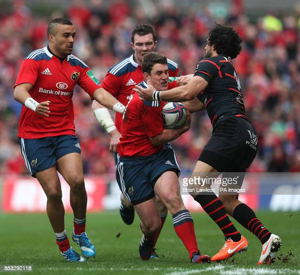 Munster's Ian Keatley supported by Simon Zebo and Peter O'Mahony against Toulouse's Yoann Huget during the Heineken Cup Quarter Final match at...