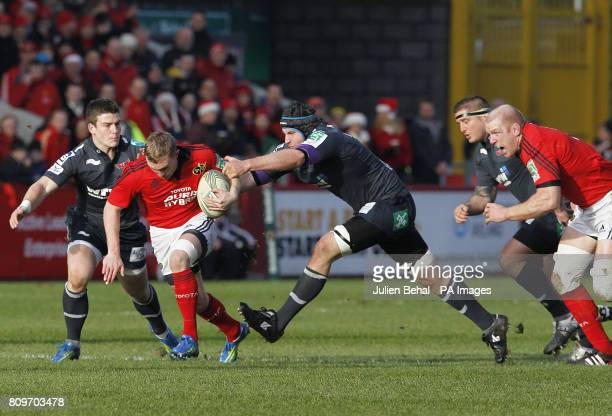Munster's Keith Earles is tackled by Scarlets' Rys Thomas and Scott Williams during the Heineken Cup match at Thomond Park Limerick Ireland