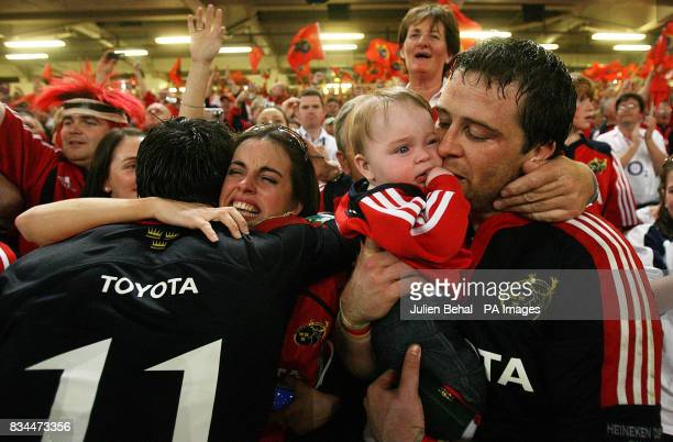 Munster's Marcus Horan kissing his baby Heather with his partner hugging team mate Ian Dowling after the Heineken Cup Final at the Millennium Stadium...