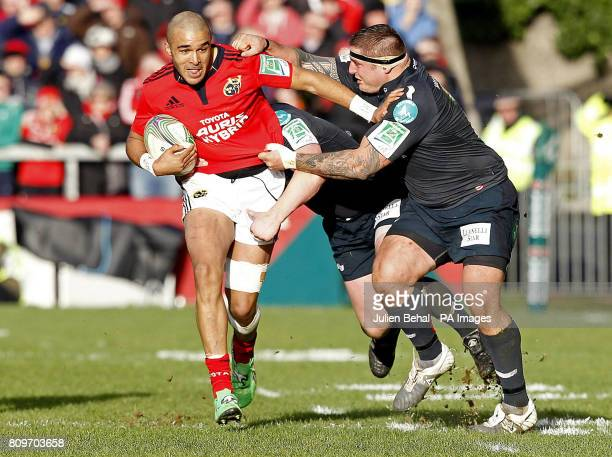 Munster's Simon Zebo is tackled by Scarlets' Rhys Thomas during the Heineken Cup match at Thomond Park Limerick Ireland