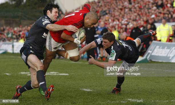 Munster's Simon Zebo is tackled by Scarlets' Stephen Jones and Rhys Priestland during the Heineken Cup match at Thomond Park Limerick Ireland