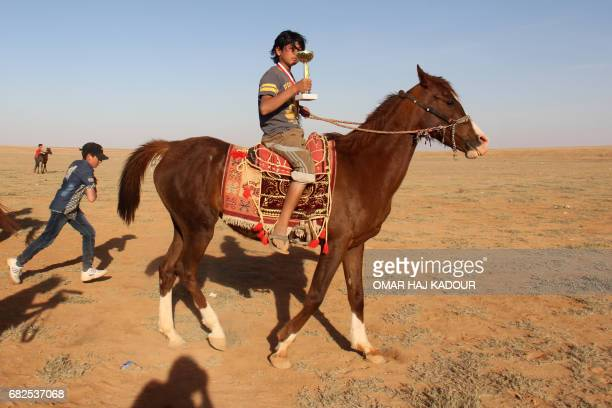 Munzir Jahjah carries a trophy as he celebrates his victory during a horse race for thoroughbred Arabian horses sponsored by Turkish NGO IHH on May...
