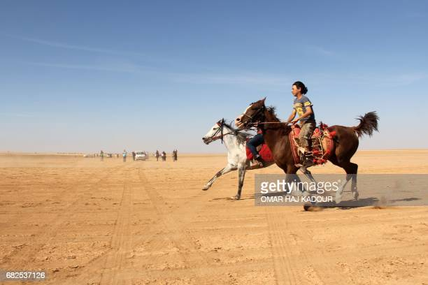 Munzir Jahjah crosses the finish line during a horse race for thoroughbred Arabian horses sponsored by Turkish NGO IHH on May 12 in the southern...