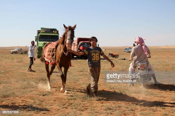 Munzir Jahjah walks with his horse following his victory during a horse race for thoroughbred Arabian horses sponsored by Turkish NGO IHH on May 12...