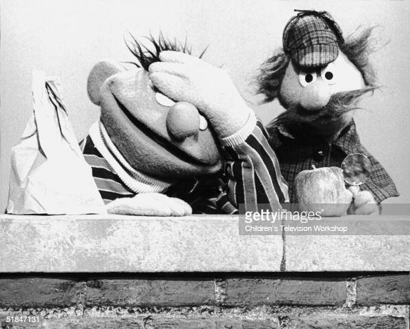 Muppet Ernie holds his hand over his eyes in exasperation as Sherlock Hemlock uses a magnifying glass to examine a bite taken out of an apple in a...