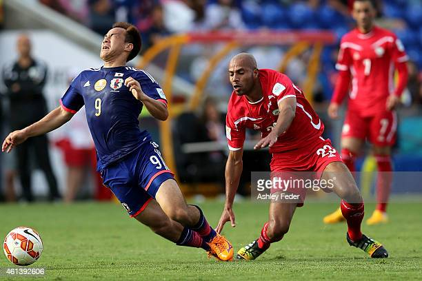 Murad Said of Palestine contests the ball against Shinji Okazaki of Japan during the 2015 Asian Cup match between Japan and Palestine at Hunter...