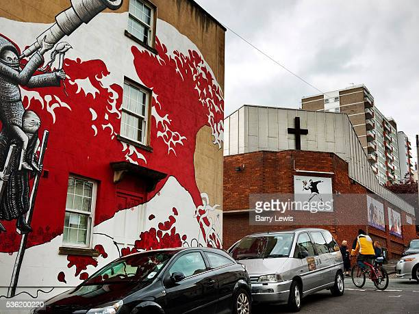 Mural based on the wave by Hokusai on Bristol Wall in front of a church with a Banksy painting