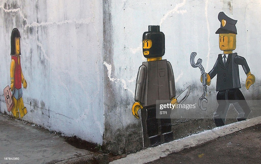 A mural by Lithuanian artist Ernest Zacharevic, which shows a Lego woman with a Chanel bag (L), a Lego robber armed with a knife (2nd, R) and a Malaysian authority member (R) is pictured in Johor Bahru on November 13, 2013. A street mural depicting a mugging involving two Lego figures was white-washed Wednesday on the orders of angry authorities in a Malaysian border city known for its crime rate and a Legoland theme park.