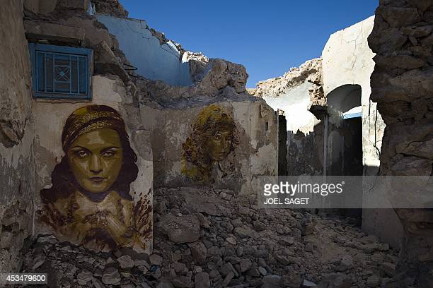 A mural by Spanish artist BToy decorates an abandoned wall in the village of Erriadh on the Tunisian island of Djerba on August 7 as part of the...