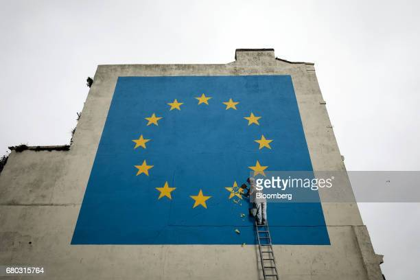 A mural depicting a European Union flag being chiseled by a workman sits on the side of a disused building near the ferry terminal in Dover UK on...