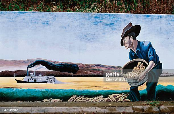 Mural depicting a man collecting cobs along the Mississippi river with a paddle wheel steamboat in the background New Orleans Louisiana United States...