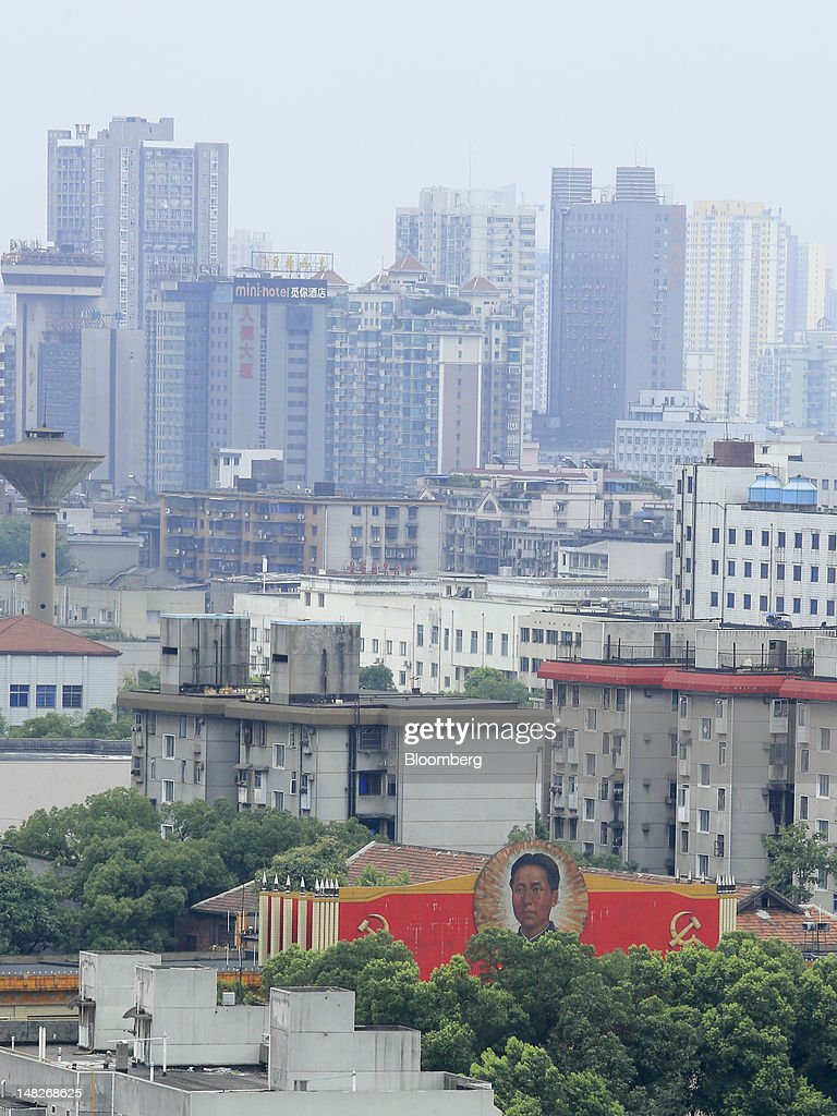 A mural depicting Mao Zedong, former leader of China, is displayed near high-rise residential and commercial buildings in Changsha, Hunan Province, China, on Friday, July 13, 2012. Gross domestic product (GDP) expanded 7.6 percent in the second quarter of 2012 from a year earlier, China's National Bureau of Statistics said today in Beijing. Photographer: Nelson Ching/Bloomberg via Getty Images
