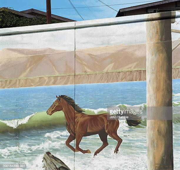 Mural on building of horse running in surf