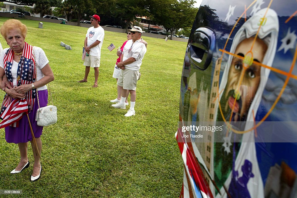 A mural showing Osama Bin Laden in crosshairs is next to people standing among veterans grave markers during a Memorial Day ceremony May 31, 2004 in Pompano Beach, Florida. The event was one of many around the country honoring those who have lost their lives fighting for the United States military.