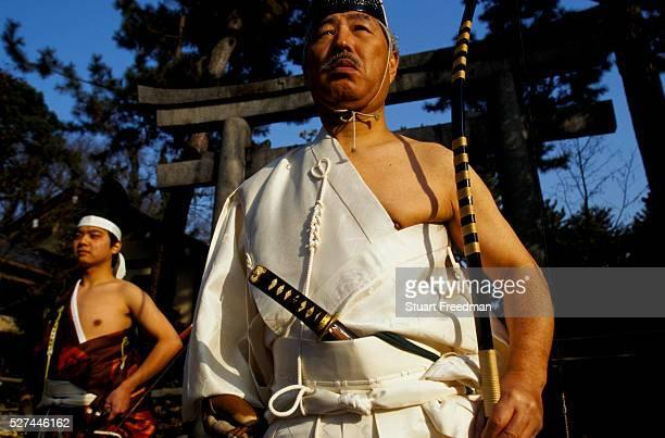 Murata Takeshi and Fujita Takehiro dressed in traditional Kyudo costumes stand at the Nashinoki Jinja Shrine Kyudo is a modern Japanese martial art...