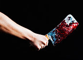 Murder or meat preparation? Hand grips blood-stained knife.