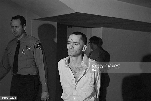 Murderer Charles Manson cleanshaven and with a short haircut is escorted through a Los Angeles courthouse by sheriff's deputies A swastika marks his...