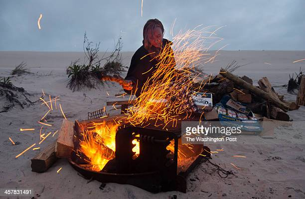 Murielle JeanPierre of Silver Spring MD moves the coals in the fire before cooking her dinner on the grill at Assateague Island National Seashore She...
