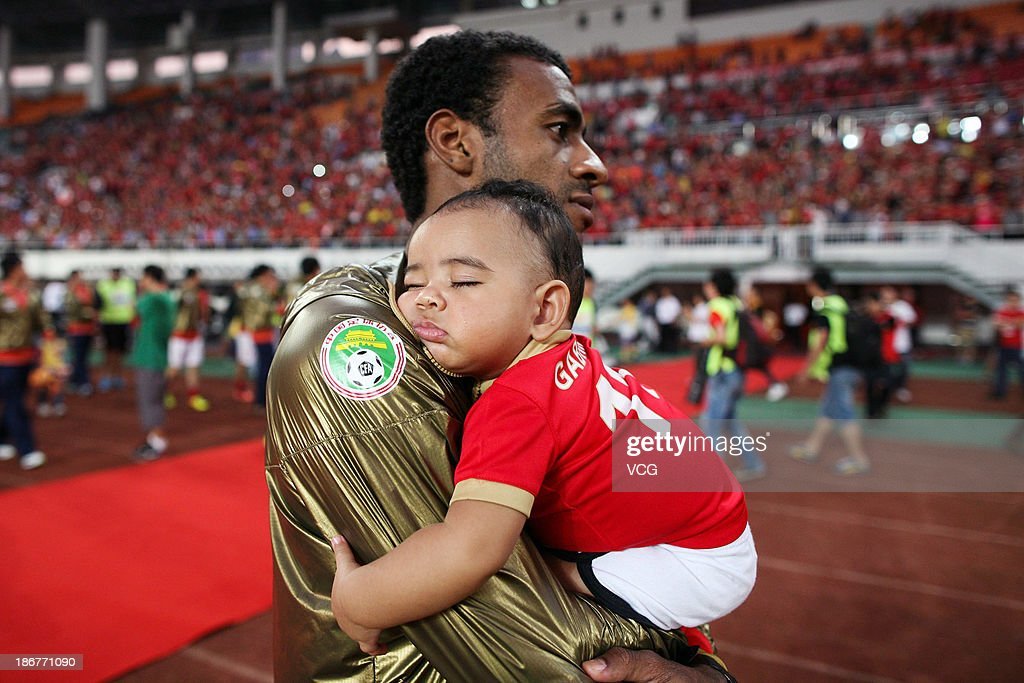 Muriqui of Guangzhou Evergrande carries his son during celebrations after his team defeated Wuhan Zall to win the 2013 Chinese Super League title at Tianhe Sports Center on November 3, 2013 in Guangzhou, China.