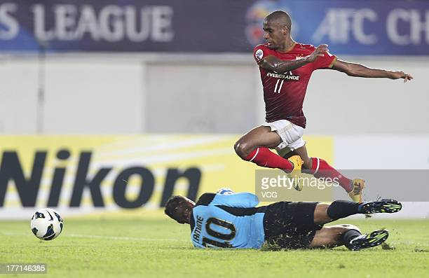 Muriqui of Guangzhou Evergrande drives the ball past goalkeeper Amine Lecomte of Lekhwiya during the AFC Champions League quarterfinal match between...