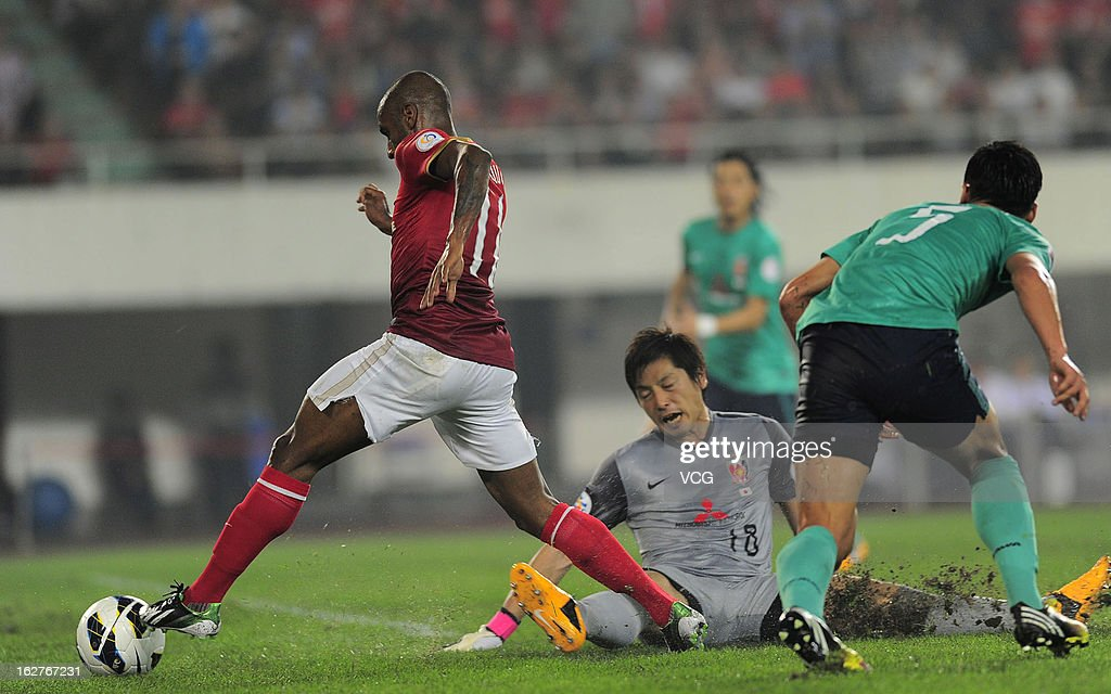 Muriqui (L) of Guangzhou Evergrande drives the ball past goalkeeper Nobuhiro Kato (C) of Urawa Red Diamonds during the AFC Champions League match between Guangzhou Evergrande and Urawa Red Diamonds at Tianhe Sports Center on February 26, 2013 in Guangzhou, China.