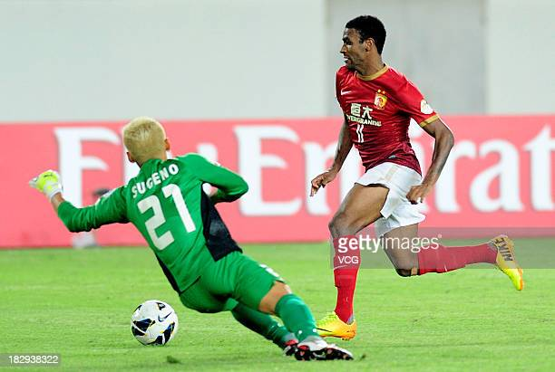 Muriqui of Guangzhou Evergrande drives the ball past goalkeeper Takanori Sugeno of Kashiwa Reysol and scores his team's fourth goal during the AFC...