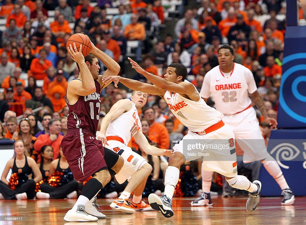 Murphy Burnatowski #13 of the Colgate Raiders attempts to pass the ball as he is guarded by Michael Carter-Williams #1, Trevor Cooney #10 and DaJuan Coleman #32 of the Syracuse Orange during the game at the Carrier Dome on November 25, 2012 in Syracuse, New York.
