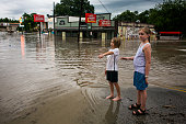 Murphy Canning and Annika Rolston watch as a street remains underwater from days of heavy rain on May 25 2015 in Austin Texas Texas Gov Greg Abbott...