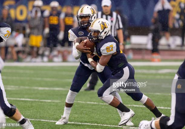Murray State quarterback Corey Newble hands the ball off to Murray State running back DJ Penick during the college football game between the Murray...
