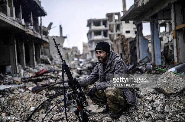 Musa a 25yearold Kurdish marksman sits in the rubble of the Syrian town of Kobane also known as Ain alArab on January 30 2015 Kurdish forces...