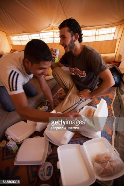 Musa Mahameed age 19 from Daara Syria eats with a friend in the Zaatari Refugee Camp Jordan in preparation for return to Syria He boarded a bus to...