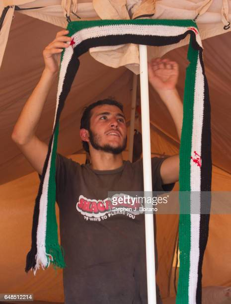 Musa Mahameed age 19 from Daara Syria hangs a scarf in the Zaatari Refugee Camp Jordan in preparation for return to Syria He boarded a bus to the the...