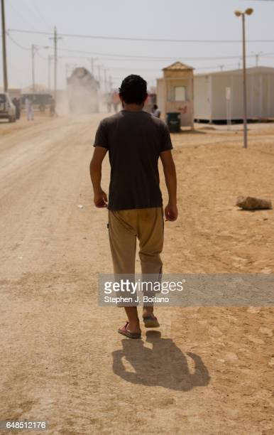 Musa Mahameed age 19 from Daara Syria walks down the road in the Zaatari Refugee Camp Jordan in preparation for return to Syria He boarded a bus to...
