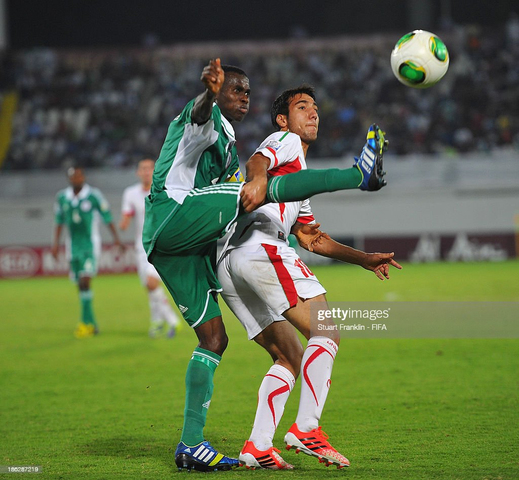 Musa Muhammed of Nigeria is challenged by Amirhossein Karim of Iran during the round of 16 match between Nigeria and Iran at Khalifa Bin Zayed Stadium on October 29, 2013 in Al Ain, United Arab Emirates.
