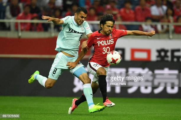 Musaev of Jubilo Iwata and Shinzo Koroki of Urawa Red Diamonds compete for the ball during the JLeague J1 match between Urawa Red Diamonds and Jubilo...
