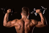 muscle bodybuilder man from behind lifting weights
