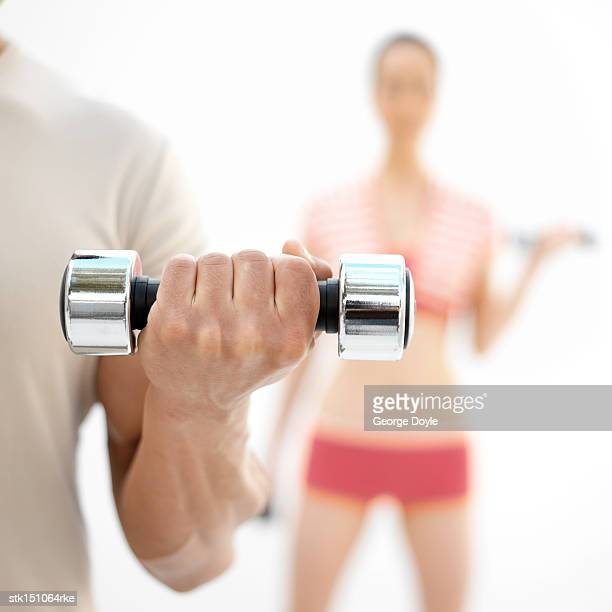 muscled arms of a man lifting dumbbells