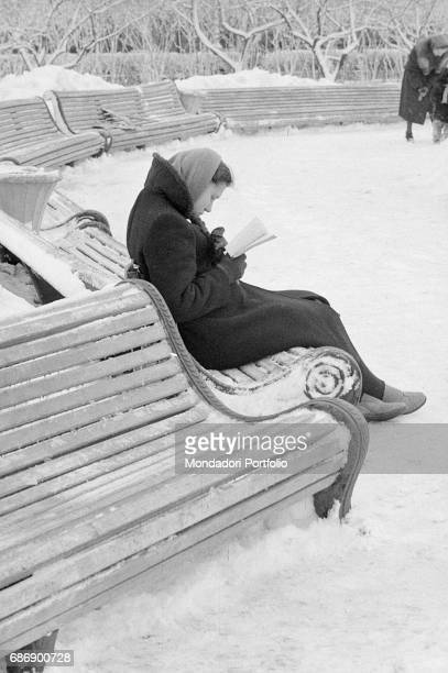 Muscovite girl reading a book on a bench covered in snow This picture is taken from the monography 'Mario De Biasi Il mio sogno Š qui' curated by...