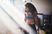 muscular african american woman sweating from work out in home gym with light rays