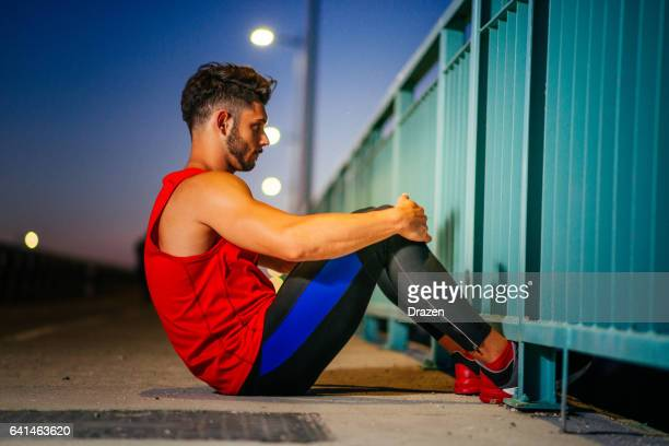 Muscular athlete exercising outdoors, near the road in urban district in summer