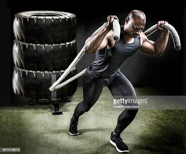 Muscular athlete pulling sled of tires.