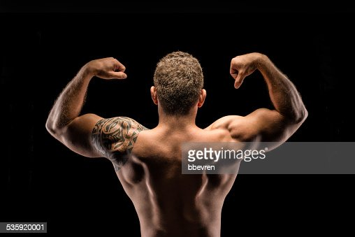 Muscular body builder posing back view : Stock Photo