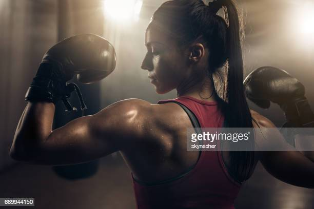 Muscular build female boxer showing her muscles in a health club.