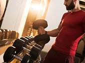 Muscular build man taking dumbbells in a gym.
