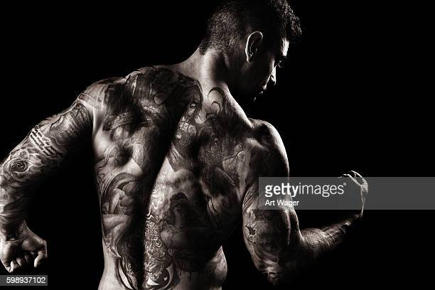 Muscular, Fully Tatooed Male Back Flexing