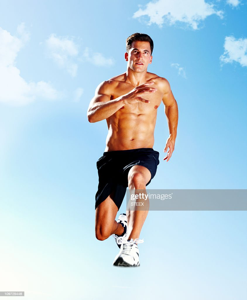 Muscular guy jumping mid-air against sky : Stock Photo